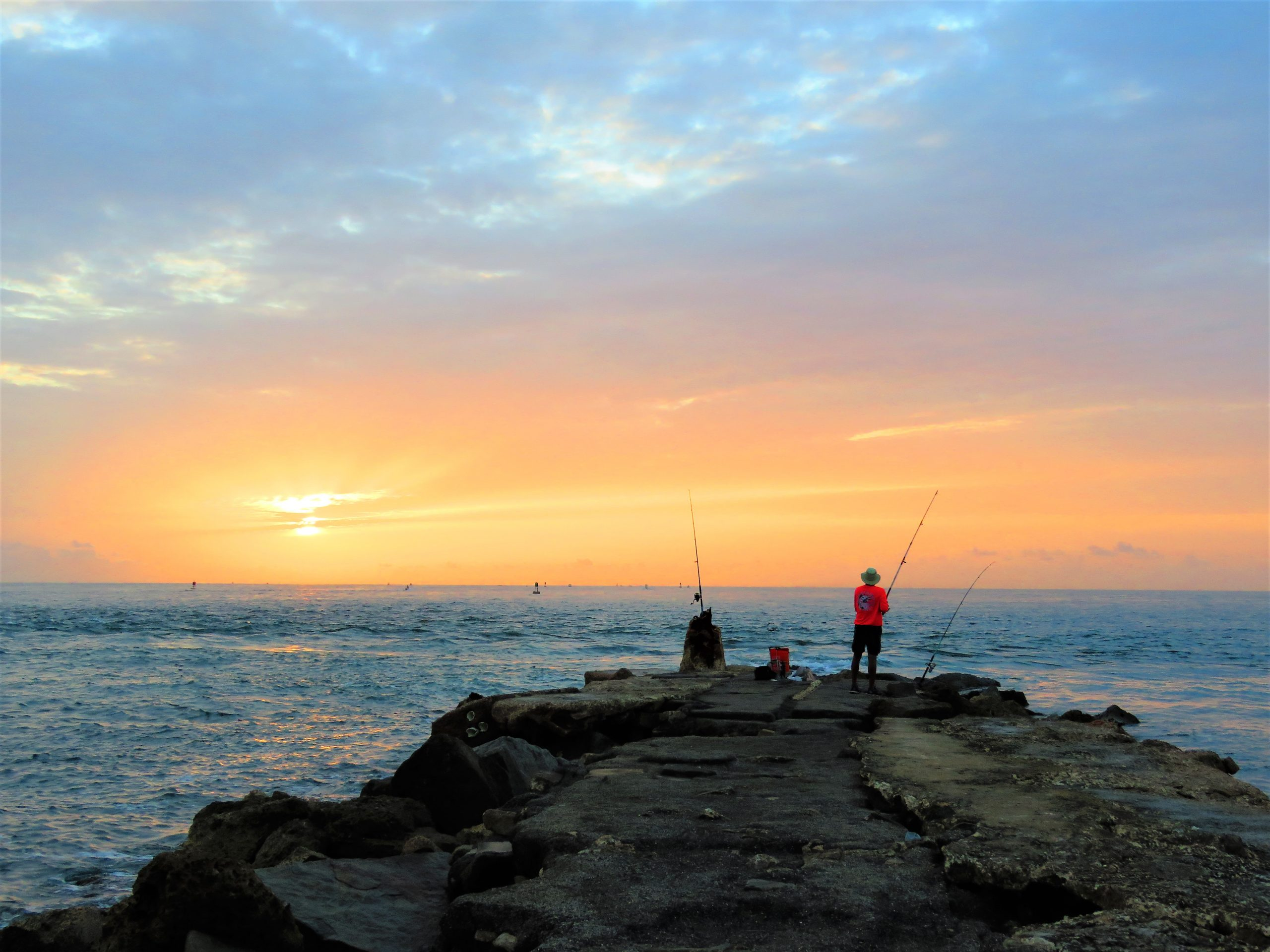 Fisherman at Dawn on the Rocky Jetty