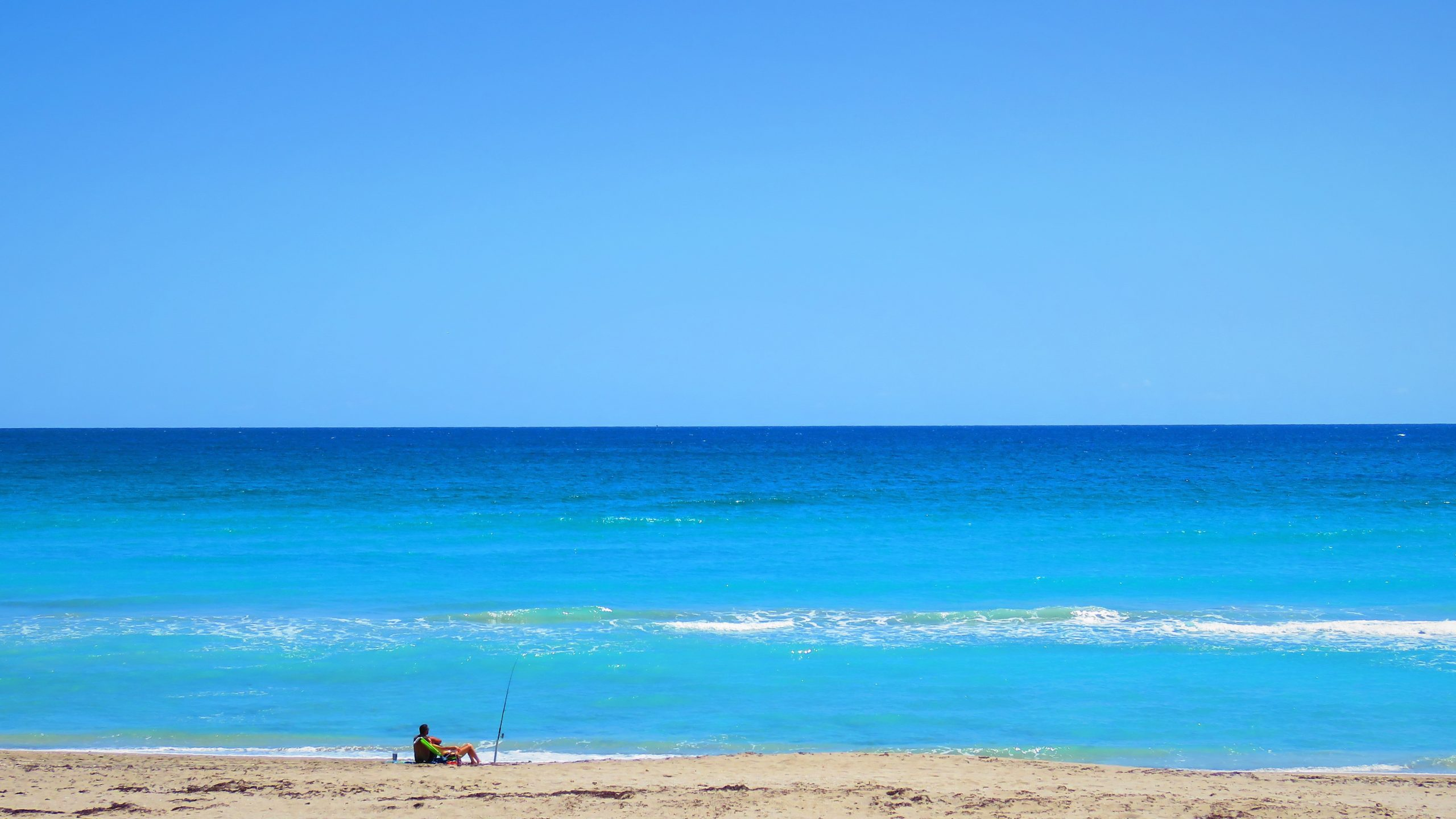 Person sitting on the beach with bright blue water