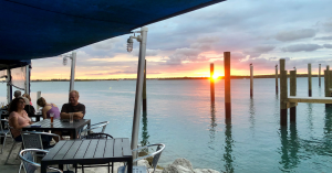 couple dining along the water and sun is setting